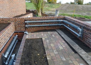 Installation of finned pipes on perimeter wall and in a heating duct for a greenhouse.